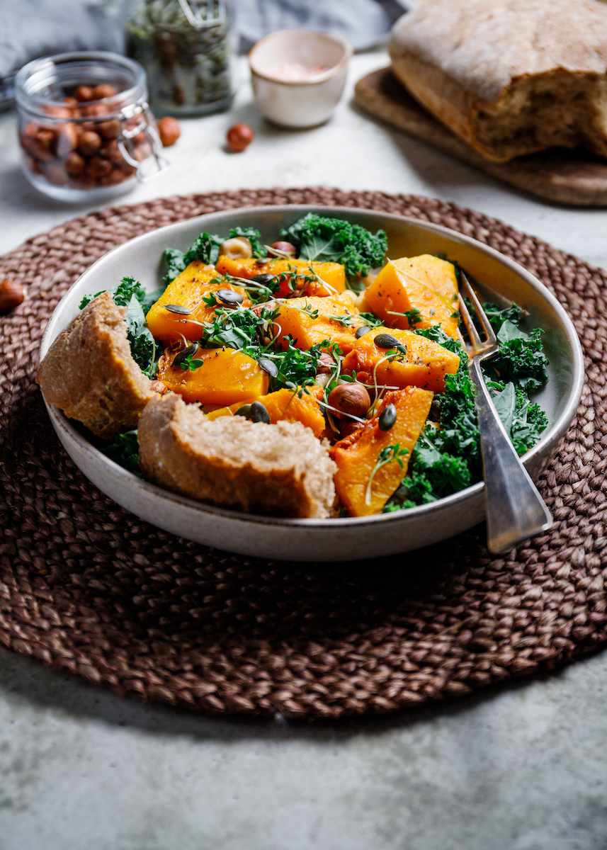 Seasonal fall salad with grilled pumpkin, kale, chickpea, pepitas and nuts. Autumn vegetarian healthy recipe.