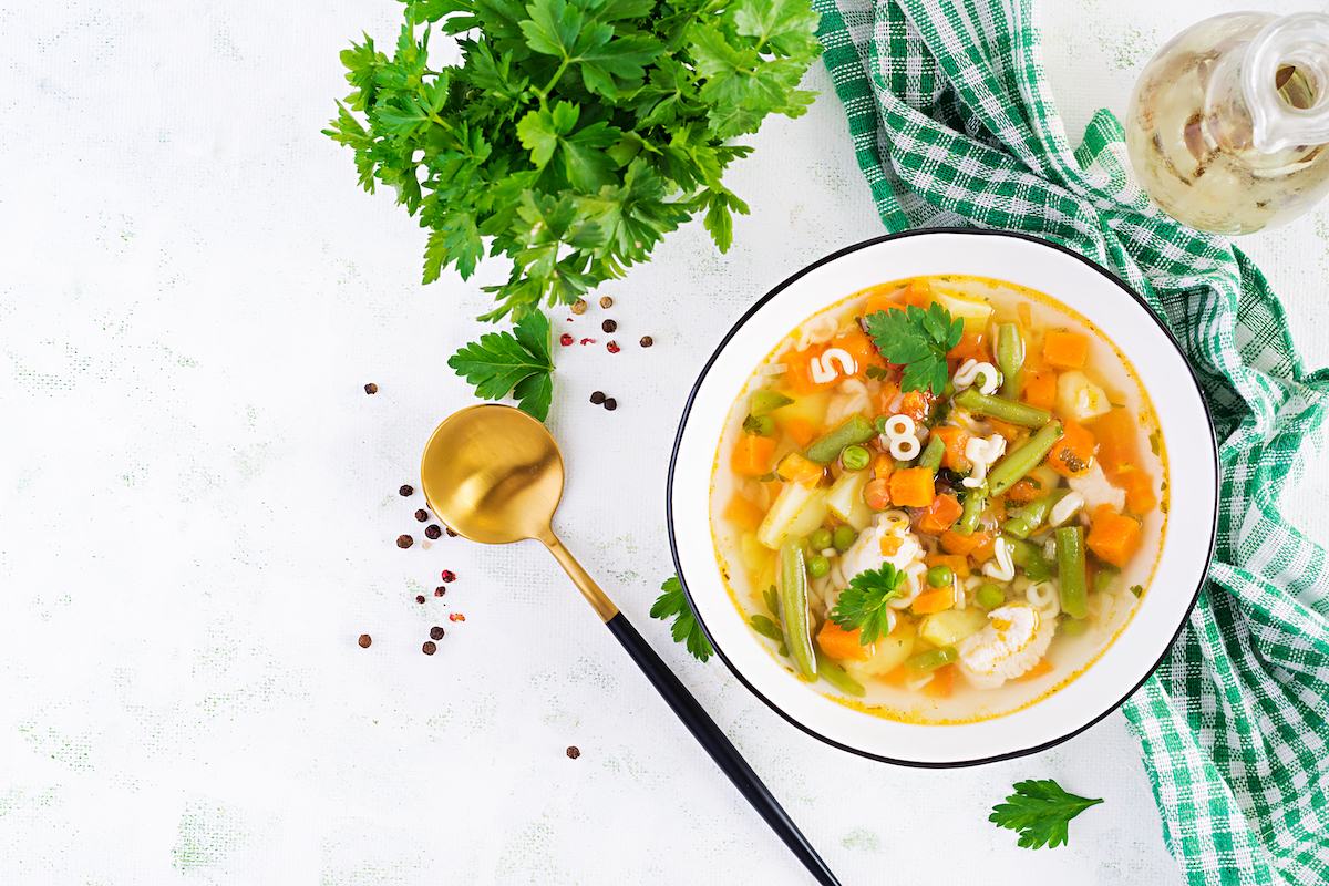 Minestrone, italian vegetable soup with pasta on light table. Top view, flat lay, copy space