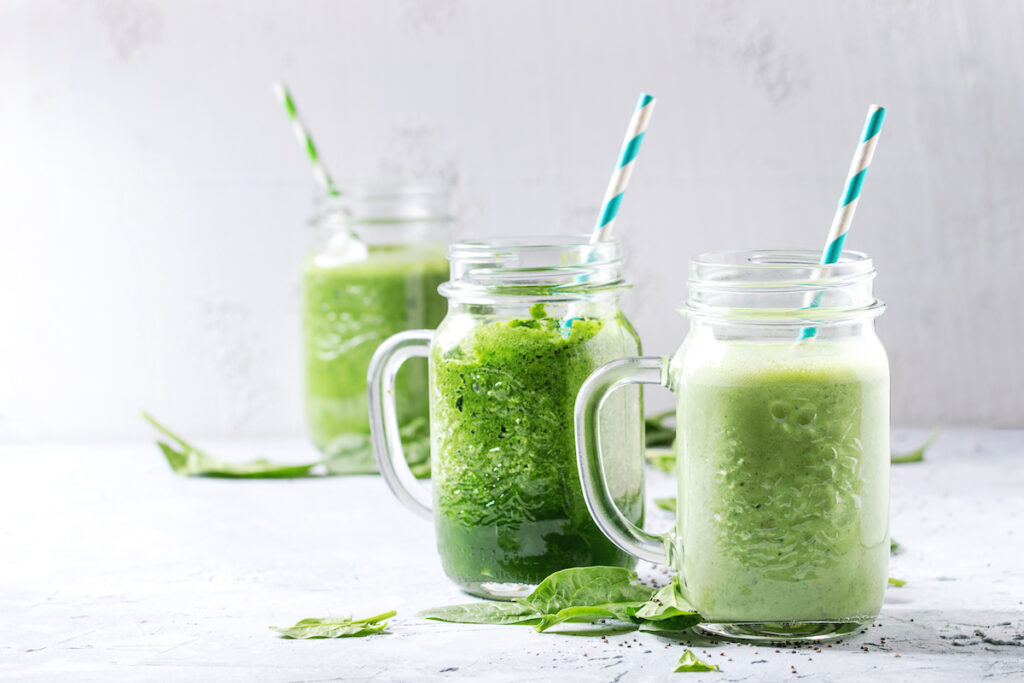 Green smoothies in mason jars with straws against a white background