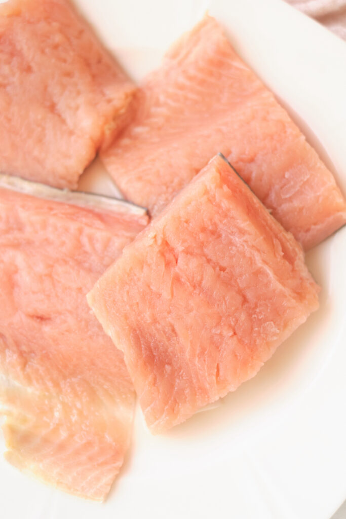 Fresh salmon fillets on a plate before baking