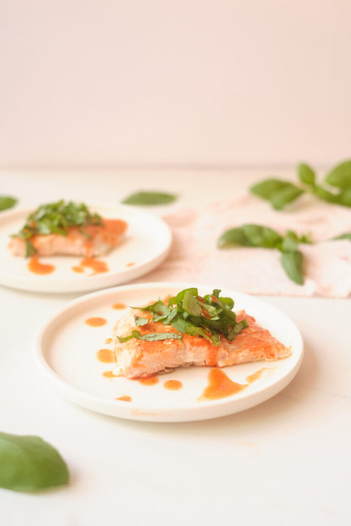 Side view of honey sriracha salmon fillets with basil, plated with basil leaves strewn about