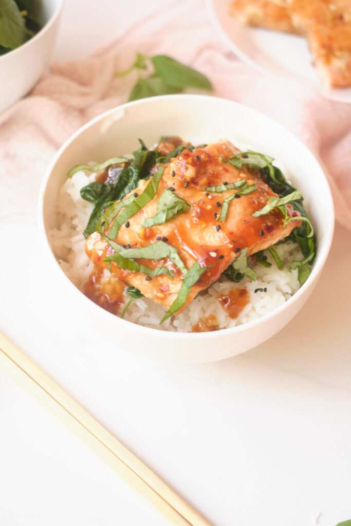 Asian rice bowl with sesame salmon, basil and spinach over rice