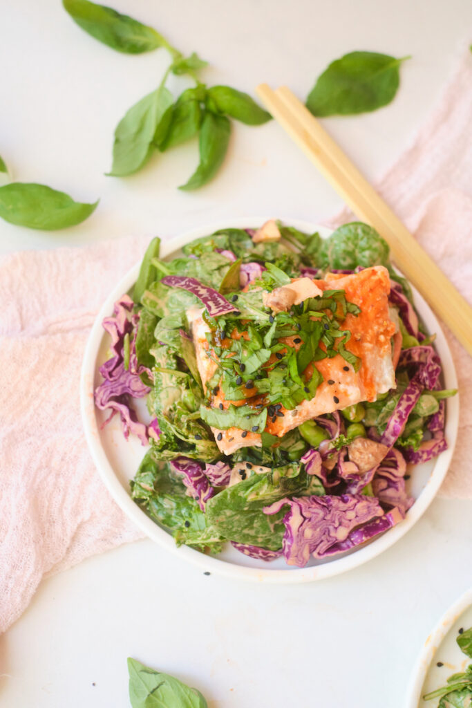 A fillet of salmon piled with fresh basil sits atop an asian sesame salad with fresh veggies