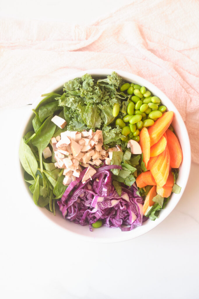 Ingredients for an asian sesame salad with cabbage, basil, spinach, salmon, edamame, kale, and mushrooms in a bowl