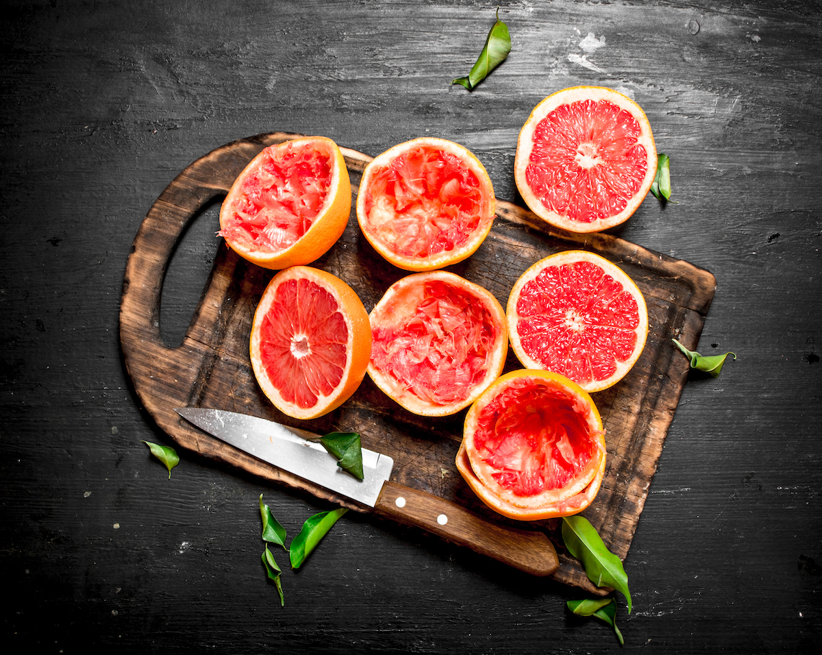 Grapefruits halves, some of which have been squeezed, on a cutting board against a black background