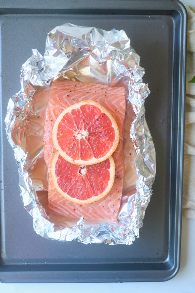 salmon fillet on a tin foil sheet and baking tray before baking and topped with grapefruit slices