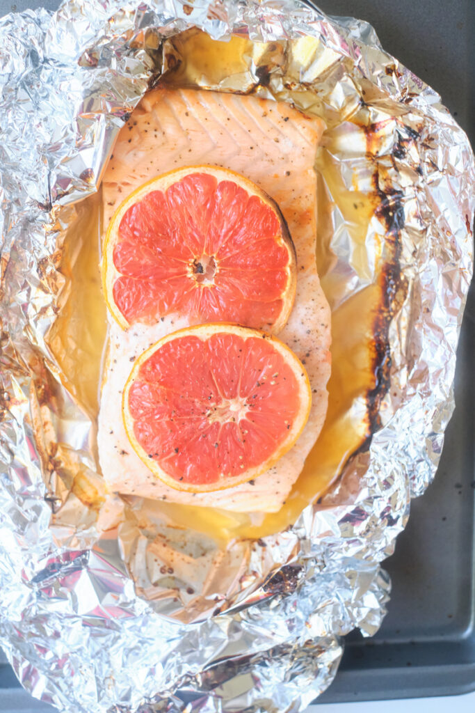 baked grapefruit salmon with grapefruit slices in a tin foil wrap