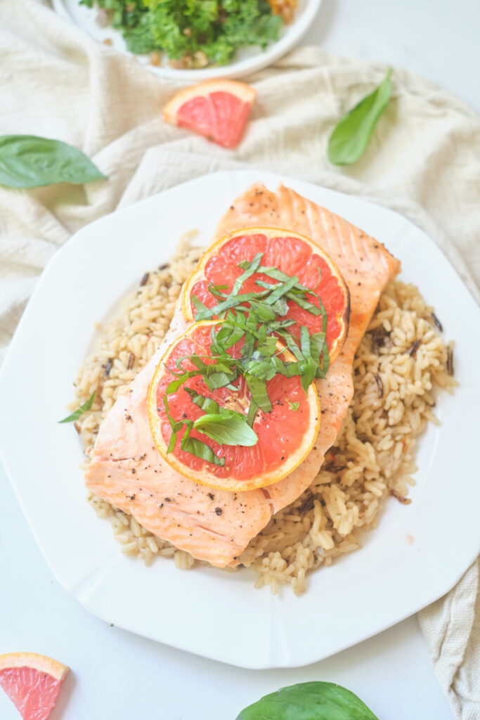 baked grapefruit salmon with grapefruit slices and basil chiffonade on a plate over brown rice with basil and grapefruit triangles strewn about