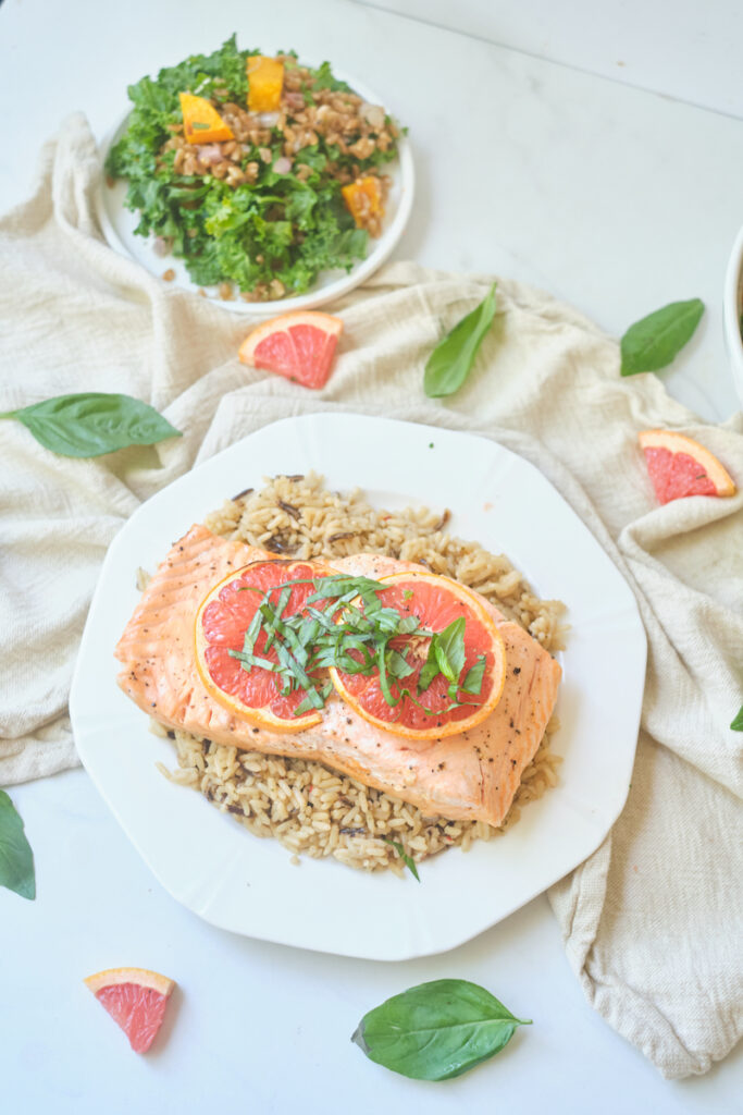 baked grapefruit salmon with grapefruit slices and basil chiffonade on a plate over brown rice, with a hearty salad in the background